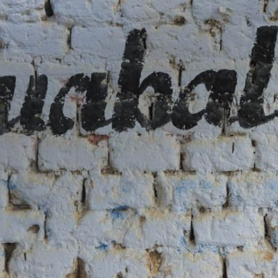 """A hand-painted sign in one of the green coffee towns bears the Peruvian district's name, """"Huabal""""."""